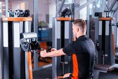 Treinamento apto do homem dos jovens consideráveis na máquina moderna da fileira no gym Fotos de Stock