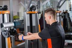 Treinamento apto do homem dos jovens na máquina da fileira Imagens de Stock Royalty Free