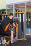 Treinamento apto do homem na máquina da fileira no gym Fotos de Stock