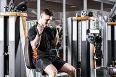 Treinamento apto do homem na máquina moderna e dar certo na sala do gym Imagem de Stock