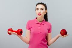 Treinamento asiático novo da mulher muscular e maçã da mão com pesos vermelhos, quilograma Fotografia de Stock