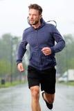 Treinamento atlético do homem mais idoso fora na chuva imagens de stock royalty free