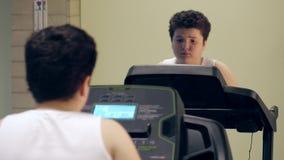 Treinamento bonito gordo pequeno excesso de peso cansado do menino na escada rolante no gym dentro video estoque