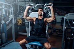 Treinamento bronzeado do homem na máquina do exercício Fotografia de Stock Royalty Free