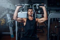 Treinamento bronzeado do homem na máquina do exercício Imagens de Stock Royalty Free
