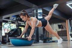 Treinamento concentrado da mulher com equipamento no gym fotografia de stock royalty free
