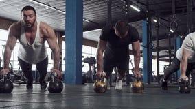 Treinamento da força no gym - amigos masculinos durante o exercício vídeos de arquivo
