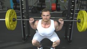 Treinamento da força no gym indivíduo que faz ocupas com um barbell halterofilista que faz o exercício com barbell video estoque