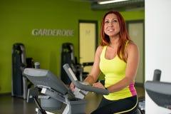 Treinamento da jovem mulher em uma bicicleta de exercício imagens de stock royalty free