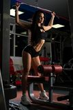 Treinamento da jovem mulher na máquina do exercício foto de stock