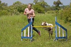 Treinamento da menina seu cão a saltar Fotografia de Stock Royalty Free