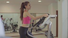 Treinamento da mulher da aptidão no instrutor transversal elíptico no clube do gym video estoque