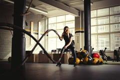 Treinamento da mulher com cordas da batalha no gym fotografia de stock