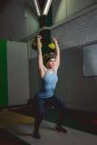 Treinamento da mulher da aptidão pelo kettlebell Jovem senhora apta que faz o exercício do crossfit Foto de Stock