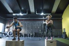 Treinamento da mulher madura e do homem novo no gym que salta no crossfit b fotos de stock