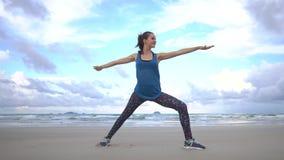 Treinamento da mulher na praia Exercícios ginásticos da manhã Conceito saudável do estilo de vida vídeos de arquivo