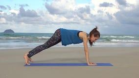 Treinamento da mulher na praia Manhã ginástica Um exercício da prancha do pé da mão uma vídeos de arquivo