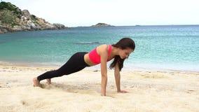 Treinamento da mulher na praia na frente do mar Manhã ginástica Exercício da prancha filme