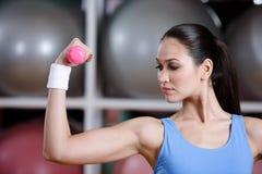 Treinamento da mulher nova com dumbbells cor-de-rosa Fotos de Stock Royalty Free