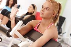 Treinamento da mulher nova na máquina do peso Fotografia de Stock