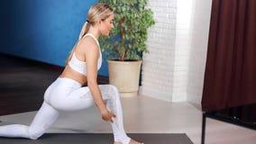 Treinamento de apreciação fêmea novo flexível dos pilates que faz o esticão do exercício no estúdio moderno da ioga filme
