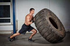 Treinamento de Crossfit - homem que lança o pneu Foto de Stock Royalty Free