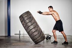 Treinamento de Crossfit - homem que lança o pneu Imagens de Stock Royalty Free