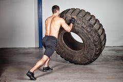 Treinamento de Crossfit - homem que lança o pneu Fotografia de Stock Royalty Free