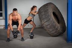 Treinamento de Crossfit - mulher que lança o pneu Imagens de Stock