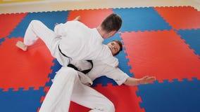 Treinamento de dois homens suas habilidades do aikido no est?dio Um homem agarra seu oponente e joga-o no assoalho fotos de stock