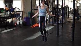Treinamento de salto da mulher em dar certo do gym Corda de salto apta da jovem mulher vídeos de arquivo