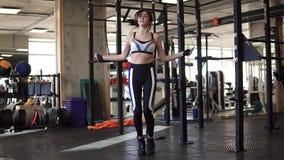 Treinamento de salto da mulher em dar certo do gym Corda de salto apta da jovem mulher video estoque