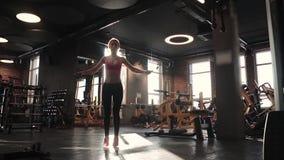 Treinamento de salto da mulher em dar certo do gym Corda de salto apta da jovem mulher filme