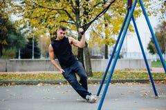Treinamento de Trx Instrutor do homem no parque que faz Excersise Exercício da aptidão Fotos de Stock Royalty Free