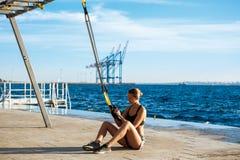 Treinamento desportivo novo da menina com trx perto do mar na manhã Fotografia de Stock Royalty Free