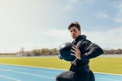 Treinamento do atleta com uma bola de medicina na pista de atletismo Fotos de Stock Royalty Free