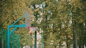 Treinamento do basquetebol fora de - um homem novo que salta e que joga uma bola e o obtém no alvo vídeos de arquivo