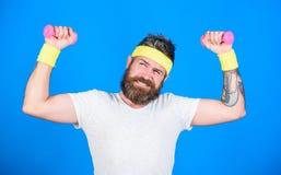 Treinamento do desportista com fundo azul dos pesos Melhore seus músculos Use pesos ou pesos Atleta farpado do homem imagem de stock royalty free