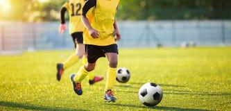 Treinamento do futebol no passo Meninos na sessão de formação do futebol Jogadores de futebol das crianças que correm a bola Fotografia de Stock