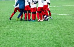 Treinamento do futebol, futebol para crianças Jogadores de futebol do menino no suporte branco e vermelho do sportswear junto no  fotos de stock royalty free
