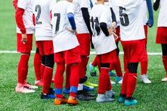 Treinamento do futebol, futebol para crianças Jogadores de futebol do menino no suporte branco e vermelho do sportswear junto no  fotografia de stock