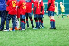 Treinamento do futebol, futebol para crianças Jogadores de futebol do menino no suporte branco e vermelho do sportswear junto no  fotografia de stock royalty free