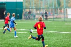 Treinamento do futebol para crianças Meninos no sportswear vermelho azul no campo de futebol Os jogadores de futebol novos pingam imagens de stock