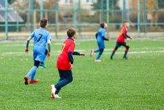 Treinamento do futebol para crianças Meninos no sportswear vermelho azul no campo de futebol Os jogadores de futebol novos pingam imagens de stock royalty free