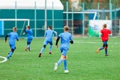Treinamento do futebol para crianças Meninos no sportswear vermelho azul no campo de futebol Os jogadores de futebol novos pingam fotografia de stock royalty free