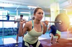 Treinamento do grupo de pessoas com os barbells no gym Fotografia de Stock Royalty Free