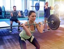 Treinamento do grupo de pessoas com os barbells no gym fotos de stock royalty free