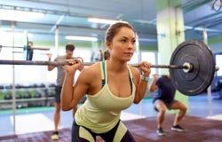 Treinamento do grupo de pessoas com os barbells no gym Imagens de Stock Royalty Free