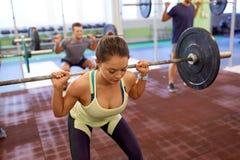 Treinamento do grupo de pessoas com os barbells no gym Imagens de Stock