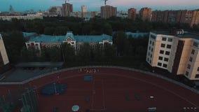 Treinamento do grupo do atleta da vista aérea na trilha do estádio do esporte na noite video estoque